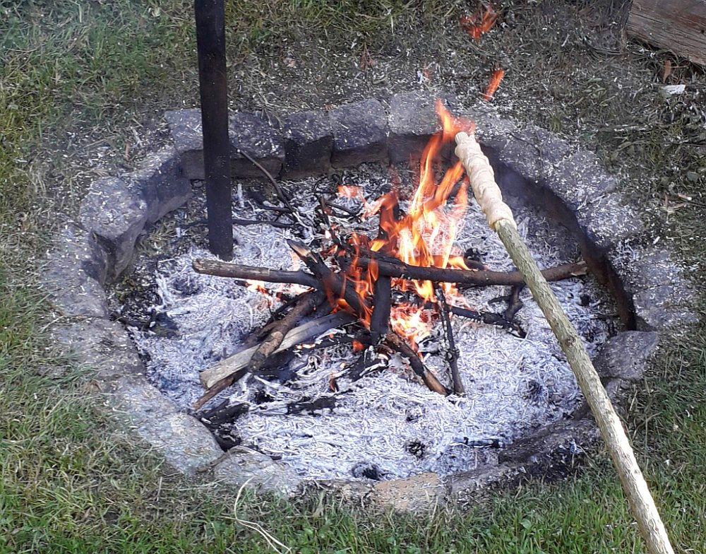 Pečení indiánského rohlíku na ohni.